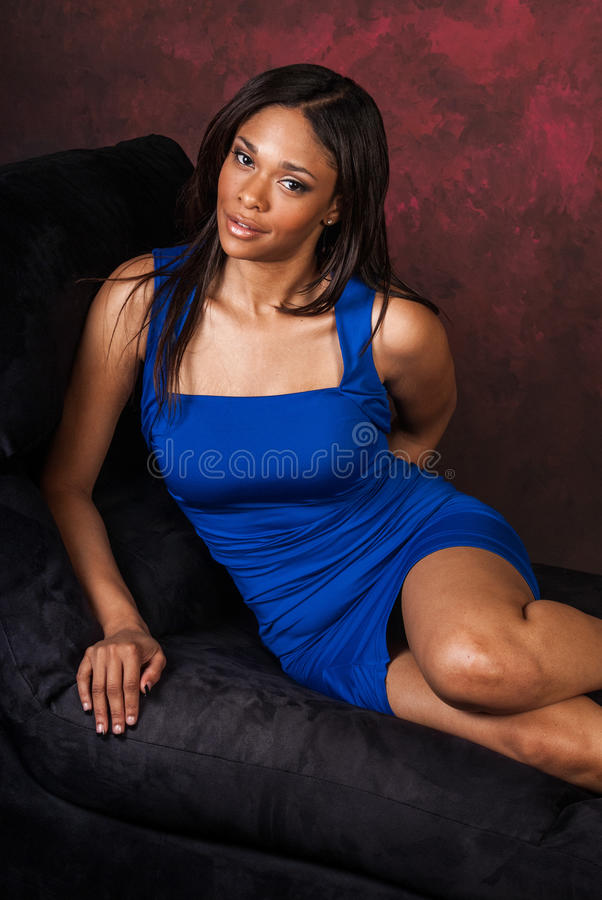African American fashion model. Curvy African American fashion model in formal blue vibrant dress royalty free stock photo