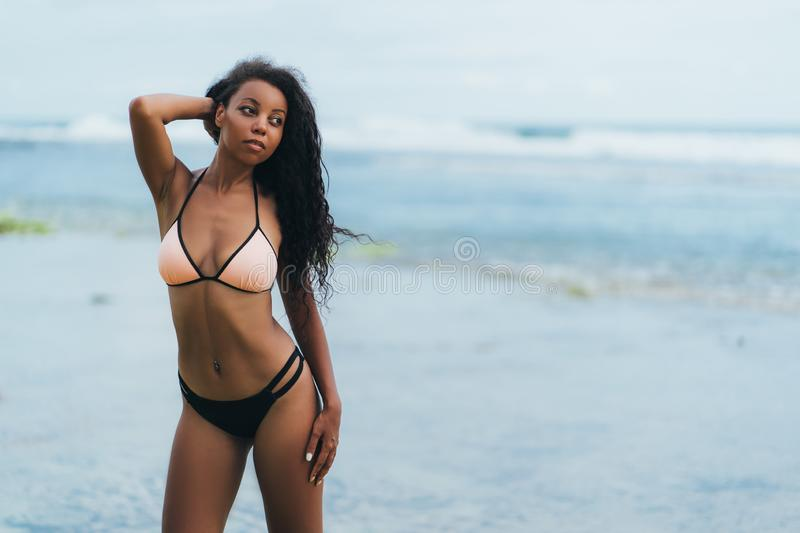 Sexy african american girl in swimwear resting on ocean beach. Young black skinned woman with curly hair stands on. Seashore. Concept swimsuit royalty free stock photos