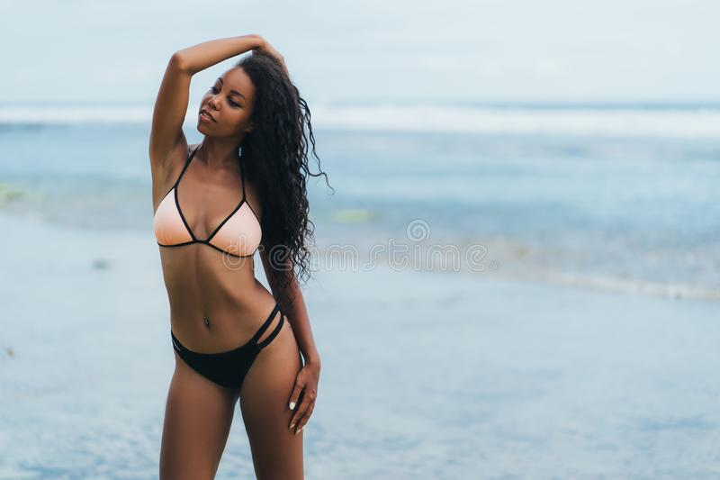 Sexy african american girl in swimwear resting on ocean beach. Young black skinned woman with curly hair stands on. Seashore. Concept swimsuit stock images