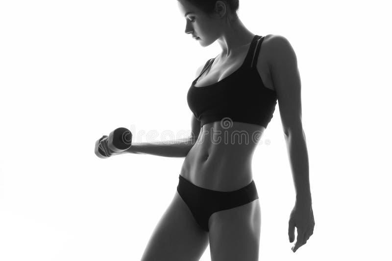 Sexy amincissez le corps convenable de femme avec des haltères Abdomen musculeux sports photo stock