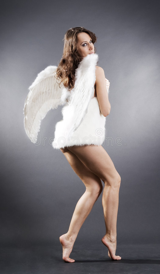 Angel in white furs. Over grey background stock photo