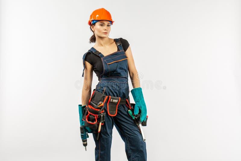 Sexy Arbeiterin im Overall und Schutzhelm mit Werkzeug schnallen das Halten der elektrischer Bohrmaschine, auf weißem Hintergrund stockfoto