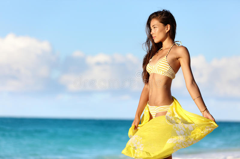 Asian bikini body woman relaxing in sunset. Asian woman with a slim stomach bikini body relaxing in sunset with yellow pareo cover-up swimwear and beachwear royalty free stock photos