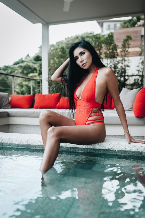 Sexy asian woman in a red swimsuit sitting at the poolside stock photography