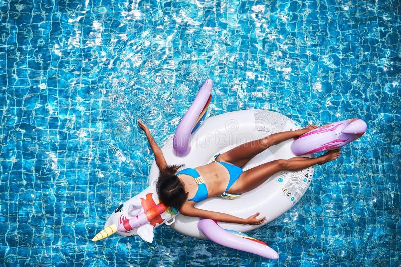 Sexy asiatische Frau, die einen Bikini tr?gt und auf dem Einhorn in einem Swimmingpool sich entspannt lizenzfreie stockbilder