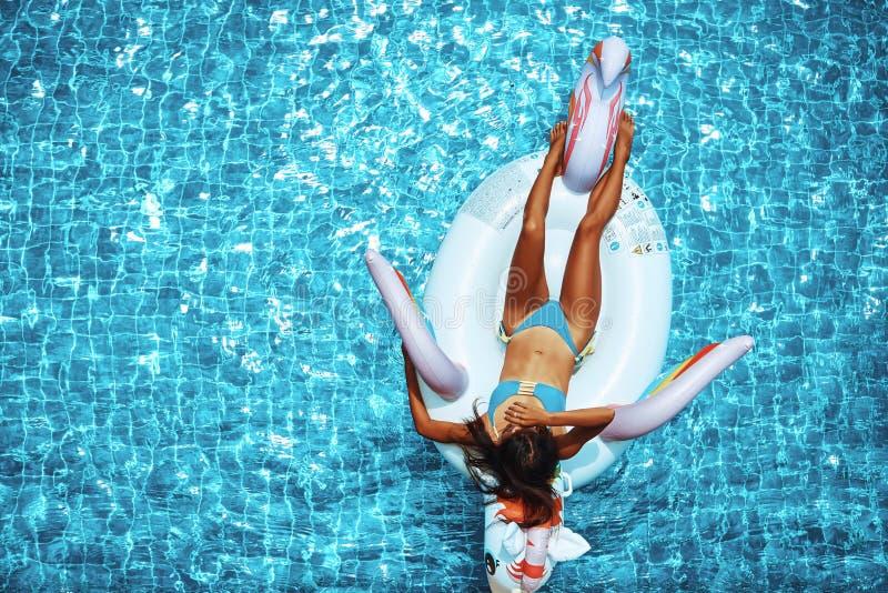 Sexy asiatische Frau, die einen Bikini tr?gt und auf dem Einhorn in einem Swimmingpool sich entspannt lizenzfreie stockfotografie
