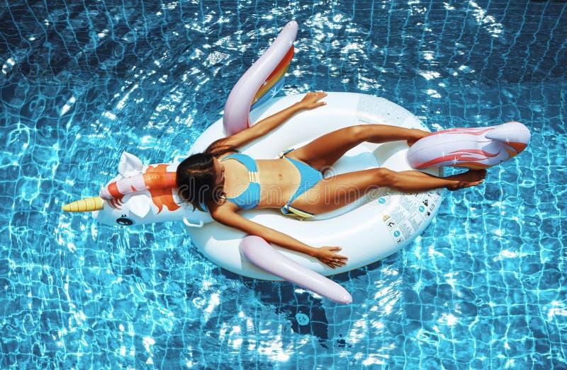 Sexy asiatische Frau, die einen Bikini tr?gt und auf dem Einhorn in einem Swimmingpool sich entspannt stockfoto