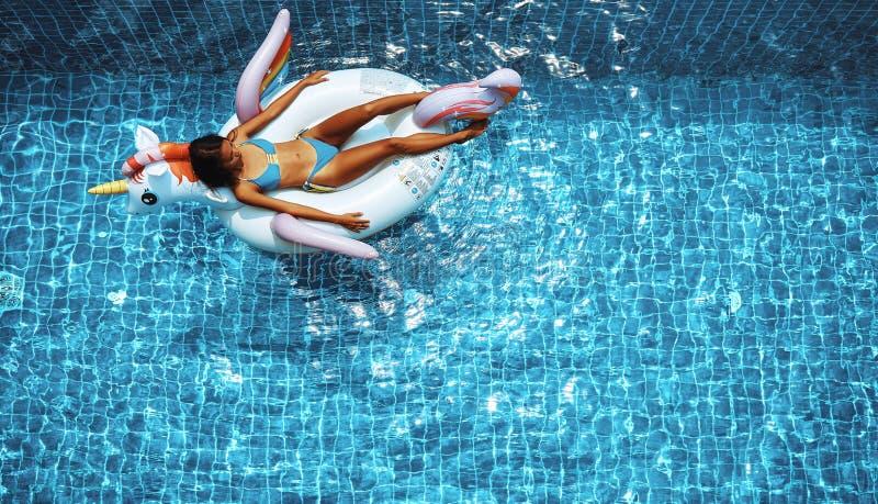 Sexy asiatische Frau, die einen Bikini tr?gt und auf dem Einhorn in einem Swimmingpool sich entspannt lizenzfreies stockfoto