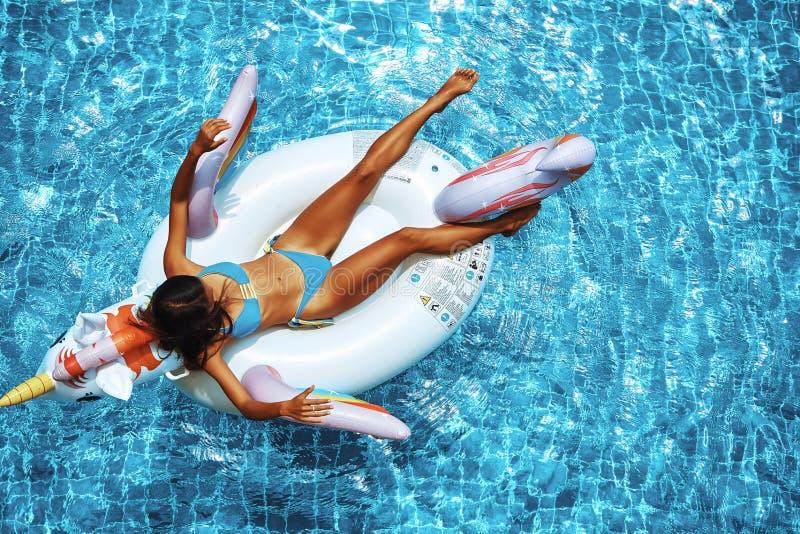 Sexy asiatische Frau, die einen Bikini tr?gt und auf dem Einhorn in einem Swimmingpool sich entspannt stockbild