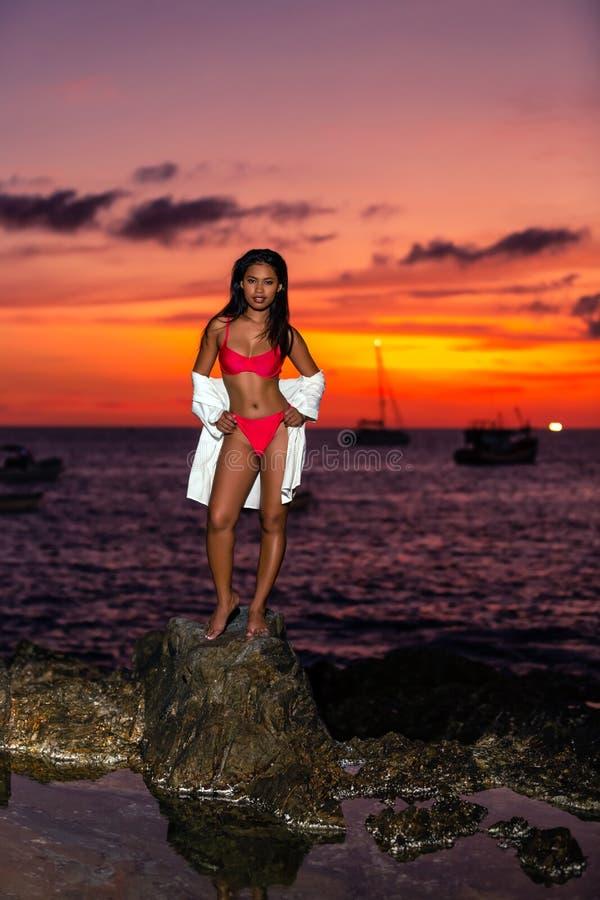 Sexy asiatisches Mädchen, das auf den Felsen bei Sonnenuntergang aufwirft lizenzfreie stockbilder
