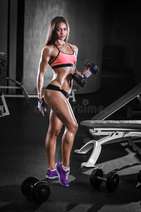 athlete girl with a dumbbell in the gym stock images