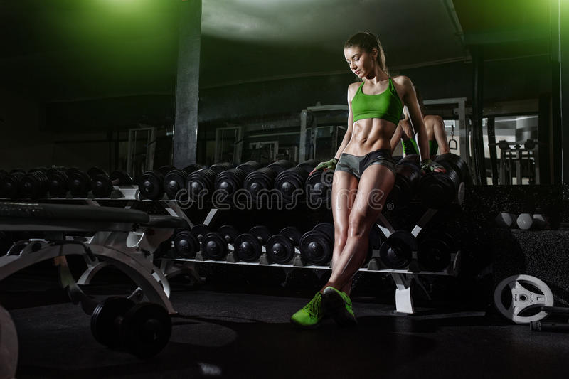 athlete girl lean on dumbbell row in gym stock photo