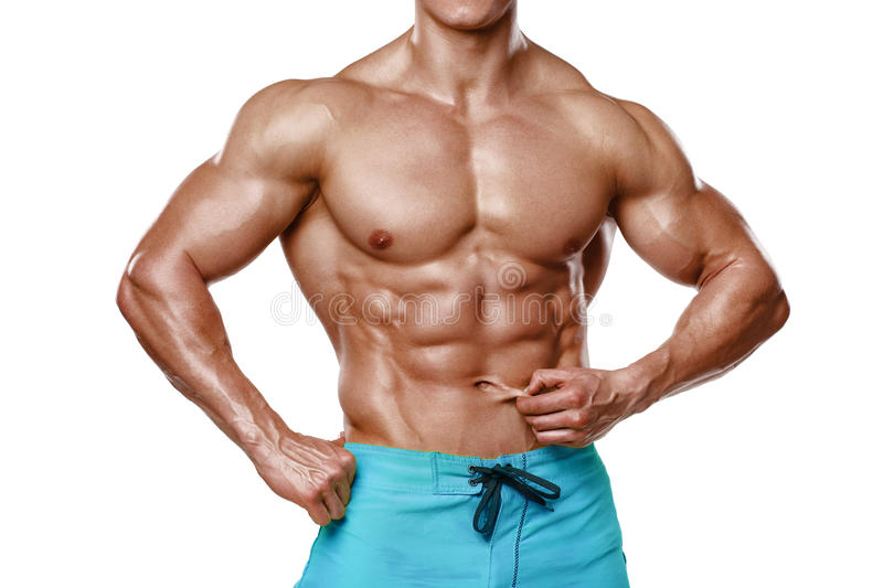 Athletic man showing abdominal muscles without fat, isolated over white background. Muscular male fitness model abs.  stock photography