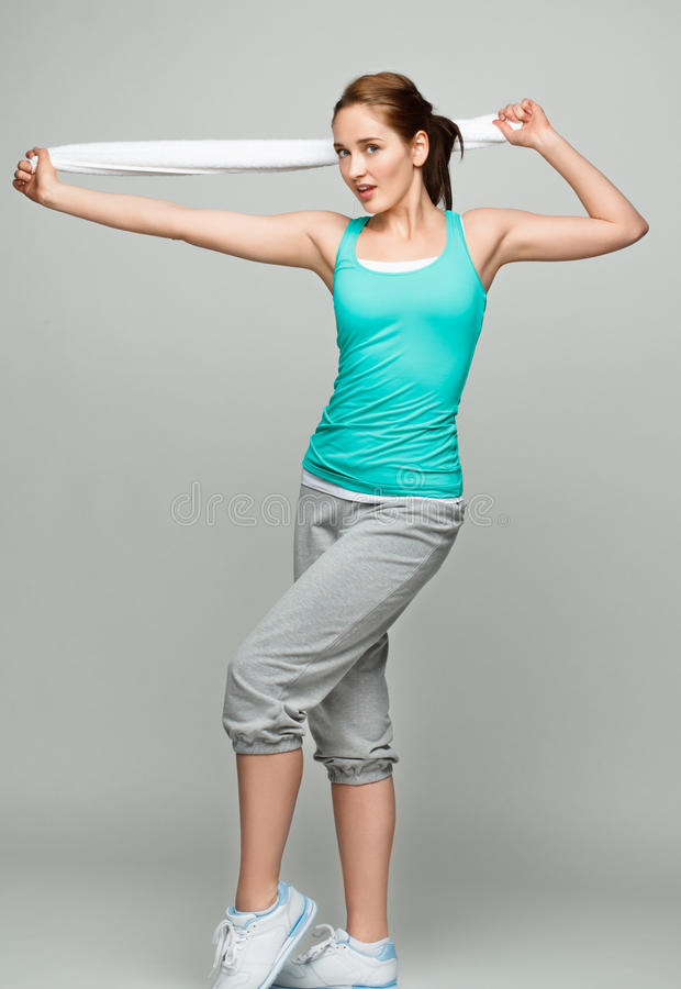 Athletic woman stretching in studio. Full length athletic woman stretching in studio royalty free stock image