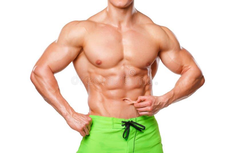 Sexy athletischer Mann, der Bauchmuskeln ohne das Fett, lokalisiert über weißem Hintergrund zeigt Muskulöse männliche Eignungsmod stockfoto