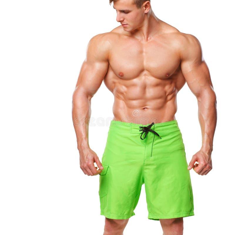 Sexy athletischer Mann, der die ABS des muskulösen Körpers und des sixpack, lokalisiert über weißem Hintergrund zeigt Starker Man lizenzfreie stockfotos
