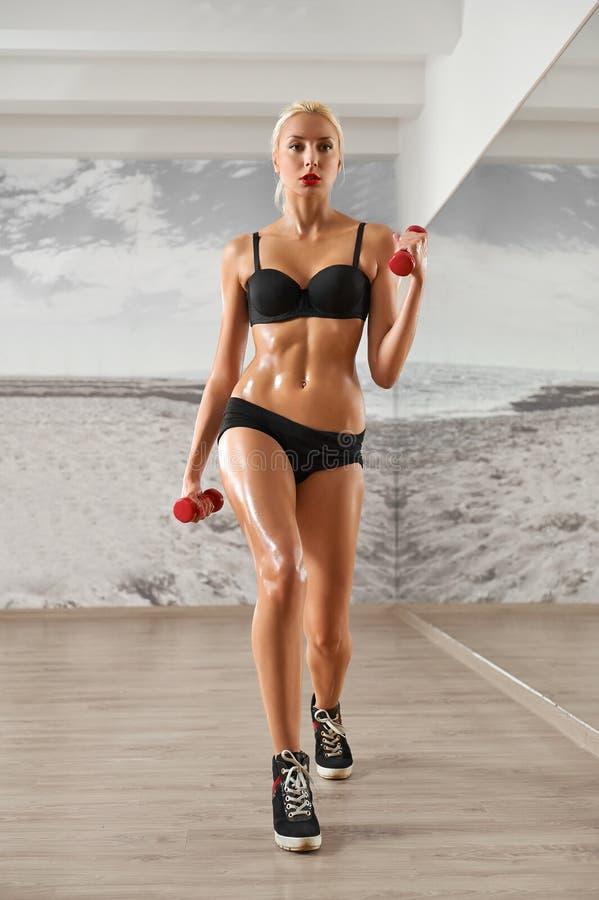 Sexy, atletisch, blondevrouw in de gymnastiek, tegen de achtergrond royalty-vrije stock fotografie