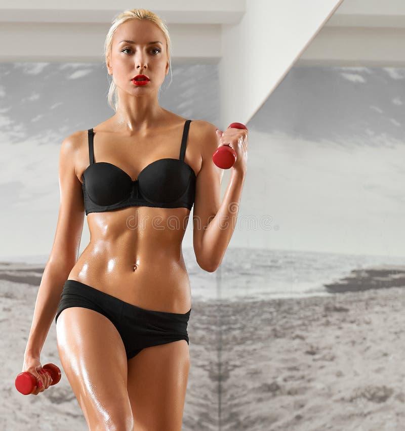 Sexy, atletisch, blondevrouw in de gymnastiek, tegen de achtergrond stock afbeelding