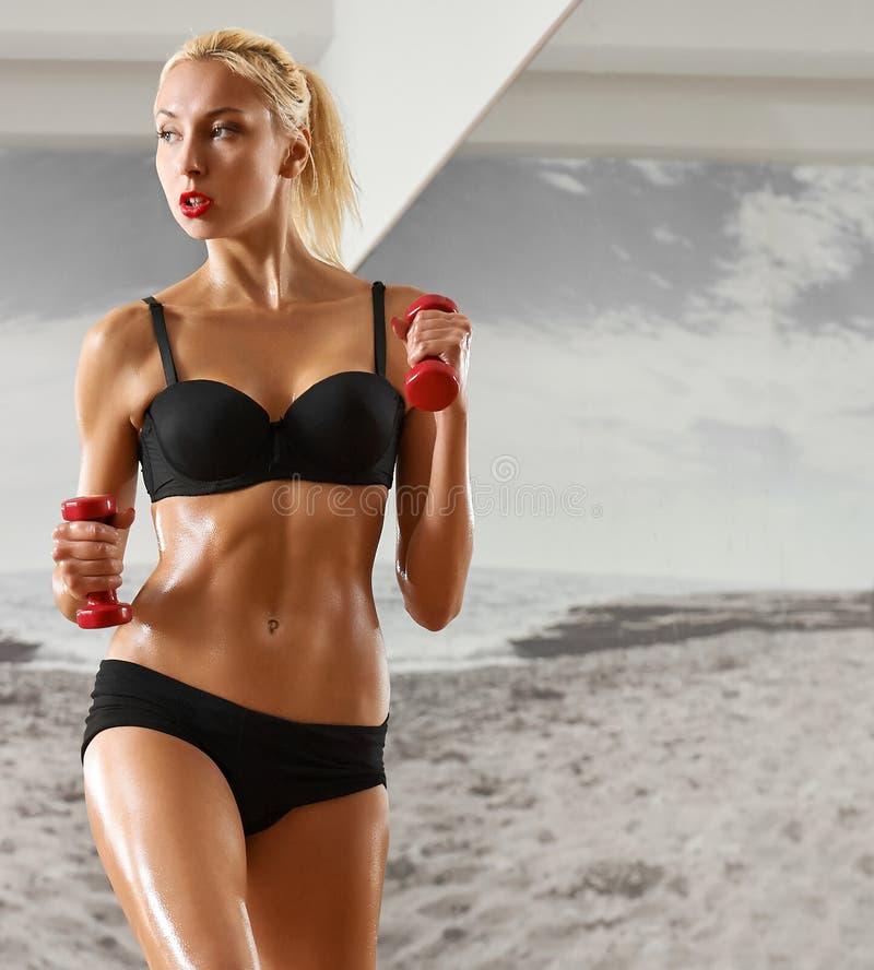 Sexy, atletisch, blondevrouw in de gymnastiek, tegen de achtergrond stock foto's