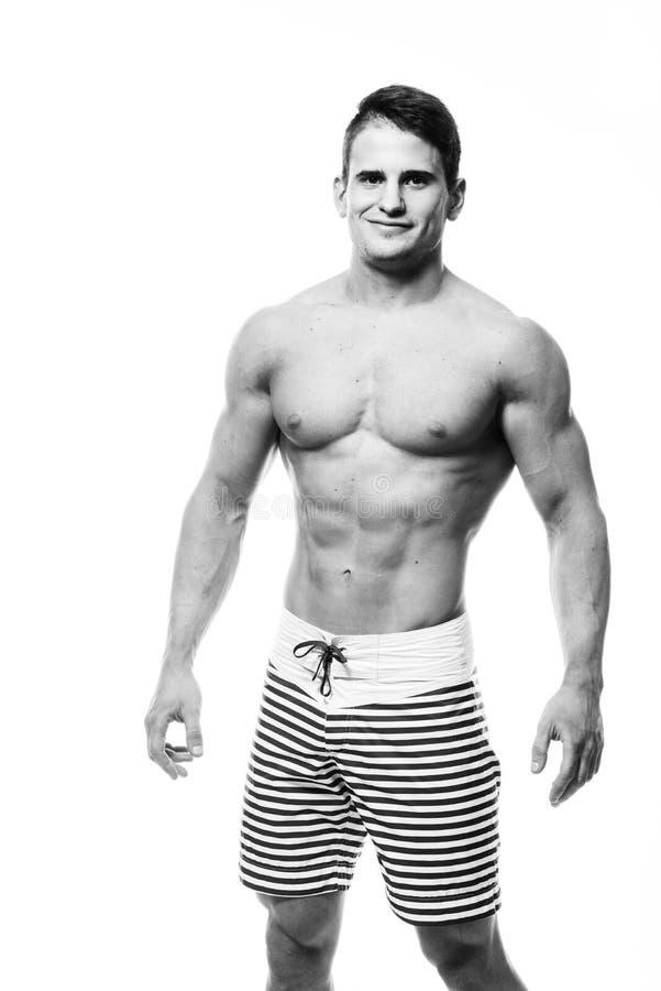 Sexy atletische mens die spierdielichaam en sixpack abs tonen, over witte achtergrond wordt geïsoleerd Het sterke mannetje nacked stock foto