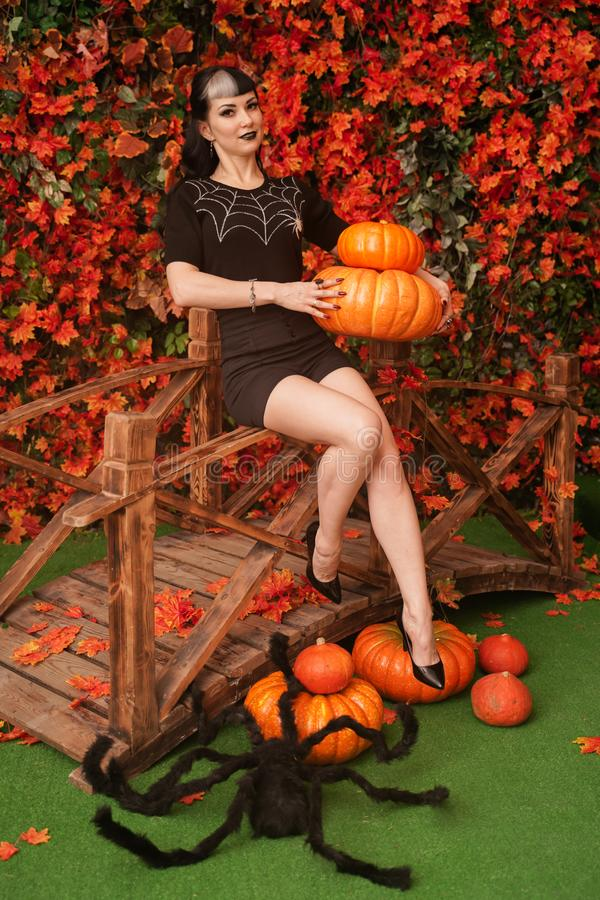 Sexy and attractive brunette witch in autumn colorful park with orange and red leaves posing with pumpkins stock photography