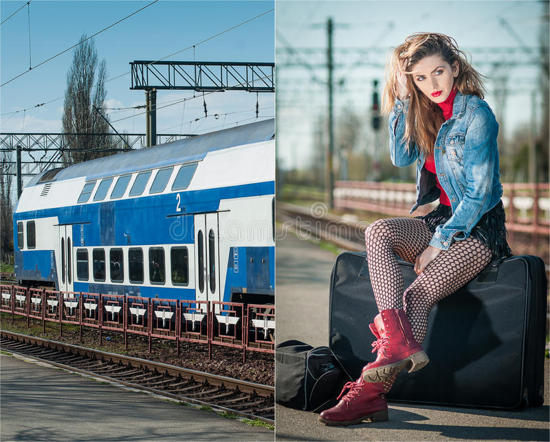 Attractive girl with red head boots posing on the platform in railway station. Blonde woman in blue jeans jacket sitting. On suitcase waiting for the train stock photography