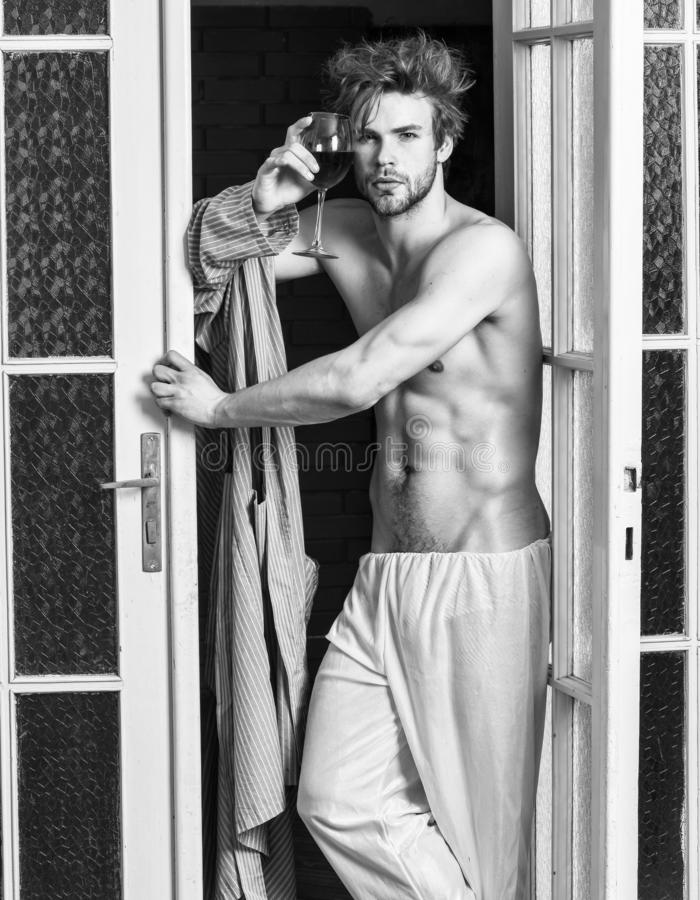 Sexy attractive macho tousled hair coming out through bedroom door. Sexy lover concept. Guy smooth skin wear bathrobe. Beginning of great evening. Man with stock photo