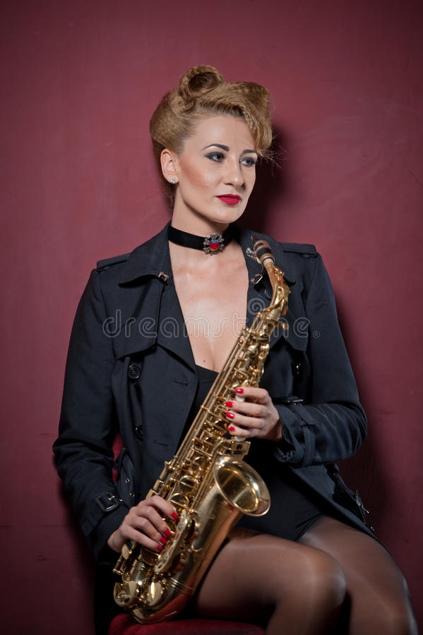 attractive woman with saxophone posing on red background. Young sensual blonde playing sax. Musical instrument, jazz stock image