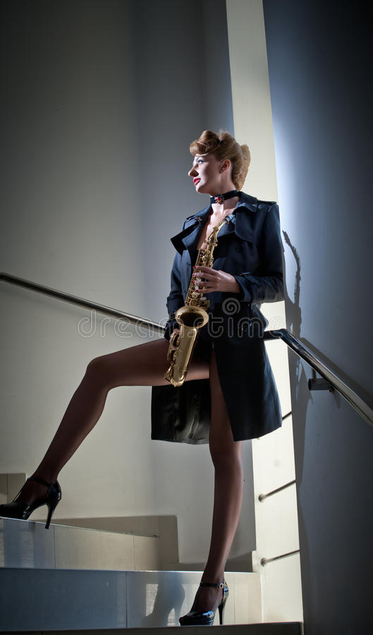 Sexy attraktive Frau mit dem Saxophon und langen Beinen, die auf Treppe aufwerfen Junges attraktives blondes spielendes Saxophon  stockfotografie