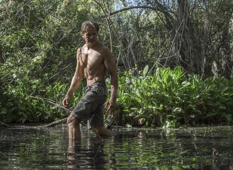 Sexy avonturenmens die door moeras waden stock fotografie