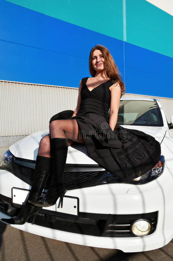 babe on the hood of a white sports car stock image
