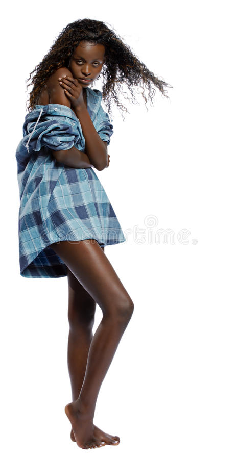 Balck woman bares her shoulder. Isolated on a white background, a young black woman with long legs up to her mans shirt, bares her shoulder as she slides off her stock photography