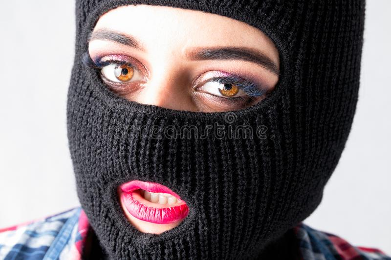 Bandit girl, fat model in balaclava, Woman Plus Size in shi. Rt posing topless on white background with brown eyes. XXL female in black mask with lips tongue royalty free stock photo