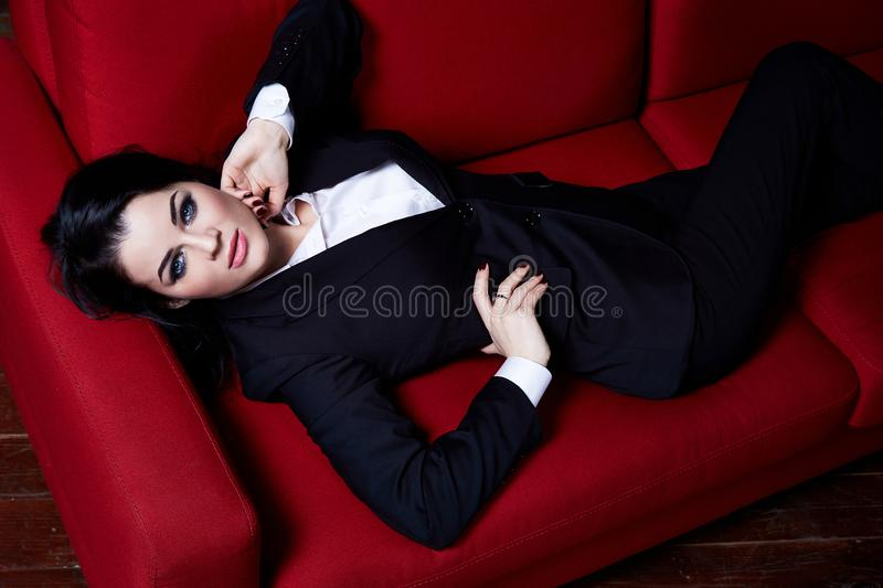 Beautiful business woman lady boss manager secretary CEO br. Unette hair bright make up sit on the red color sofa wear uniform black suit jacket trousers white stock photo