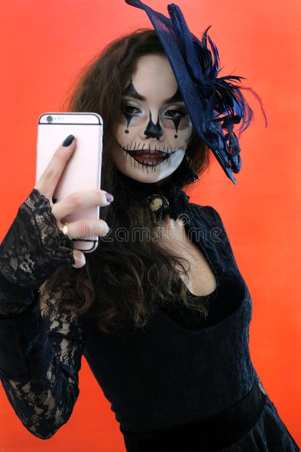 Halloween makeup for a party. girl in a black dress and hat takes pictures of herself on the phone. A woman makes a royalty free stock photo