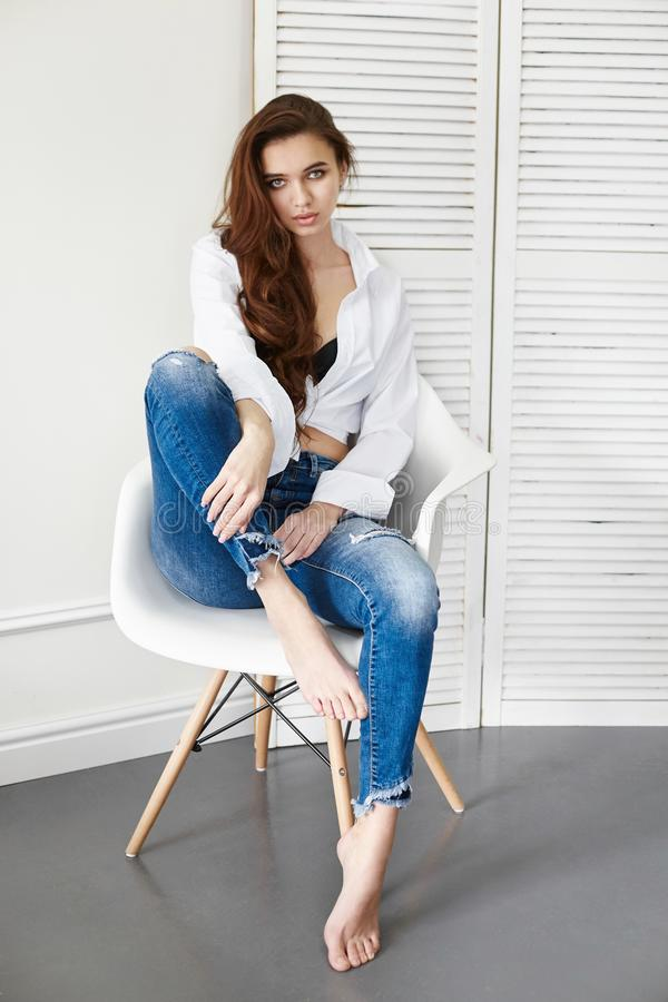 Beautiful girl in jeans white shirt sitting on a chair. Gorgeous long hair and charming eyes young woman. Business lady. Is young and confident. Girl sitting on stock photo