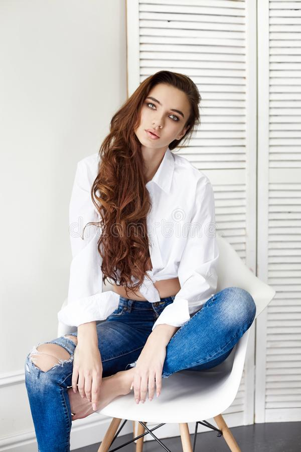 Beautiful girl in jeans white shirt sitting on a chair. Gorgeous long hair and charming eyes young woman. Business lady. Is young and confident. Girl sitting on royalty free stock image