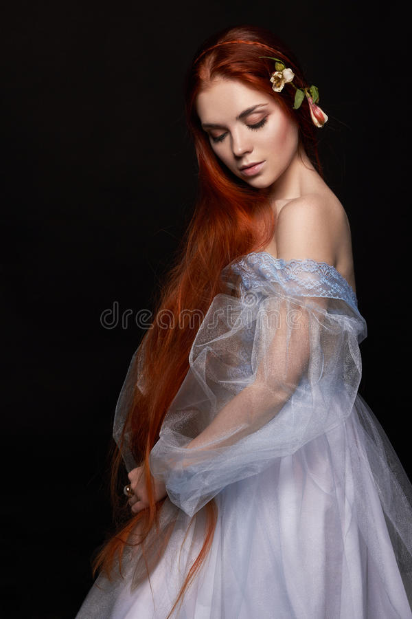 Beautiful redhead girl with long hair in dress cotton retro. Woman portrait on black background. Deep eyes. Natural beauty. Clean skin, facial care and hair stock image