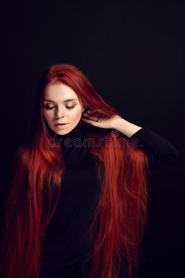 Sexy beautiful redhead girl with long hair. Perfect woman portrait on black background. Gorgeous hair and deep eyes. Natural royalty free stock photo