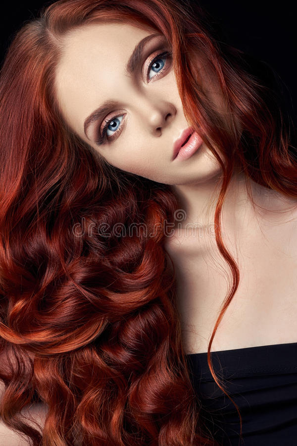 beautiful redhead girl with long hair. Perfect woman portrait on black background. Gorgeous hair and deep eyes Natural beauty stock photography