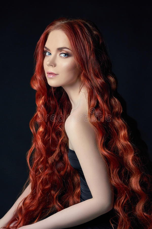 beautiful redhead girl with long hair. Perfect woman portrait on black background. Gorgeous hair and deep eyes Natural beauty stock photo