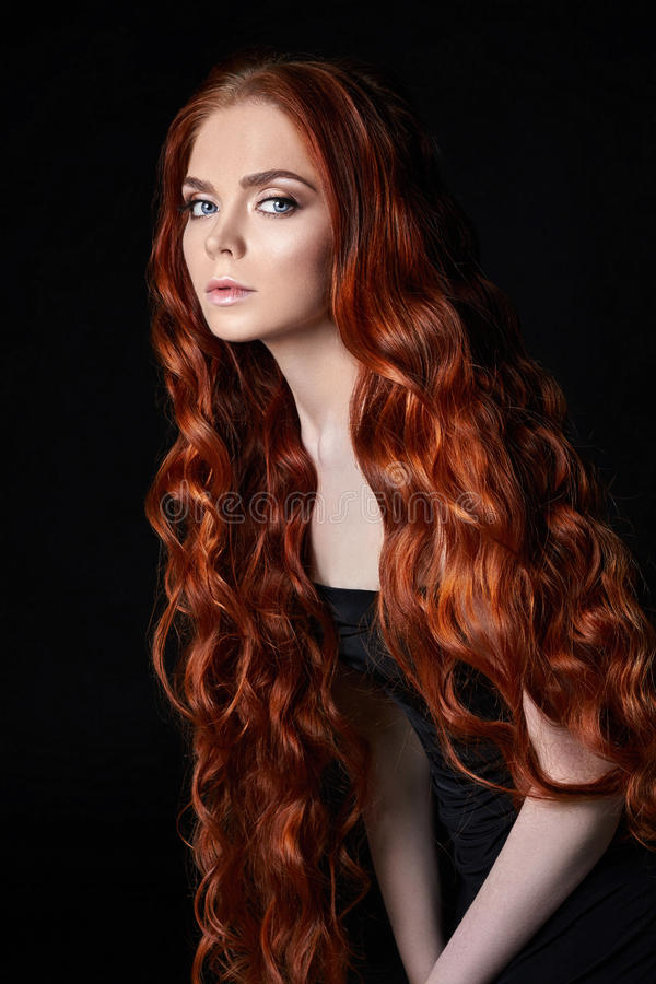 Beautiful redhead girl with long hair. Perfect woman portrait on black background. Gorgeous hair and deep eyes Natural beauty. Beautiful redhead girl with long royalty free stock image