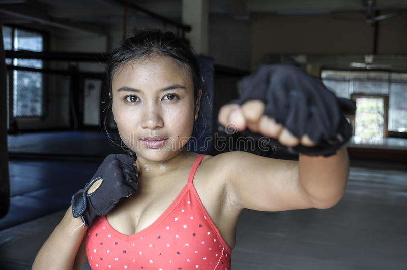 beautiful and sweaty young Asian woman in sport cloths and fighting gloves throwing punch stock photo