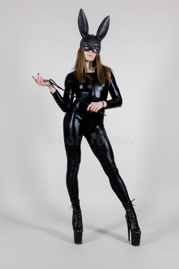 beautiful woman pole dancer posing in latex costume and black rabbit mask on background. Easter bunny concept