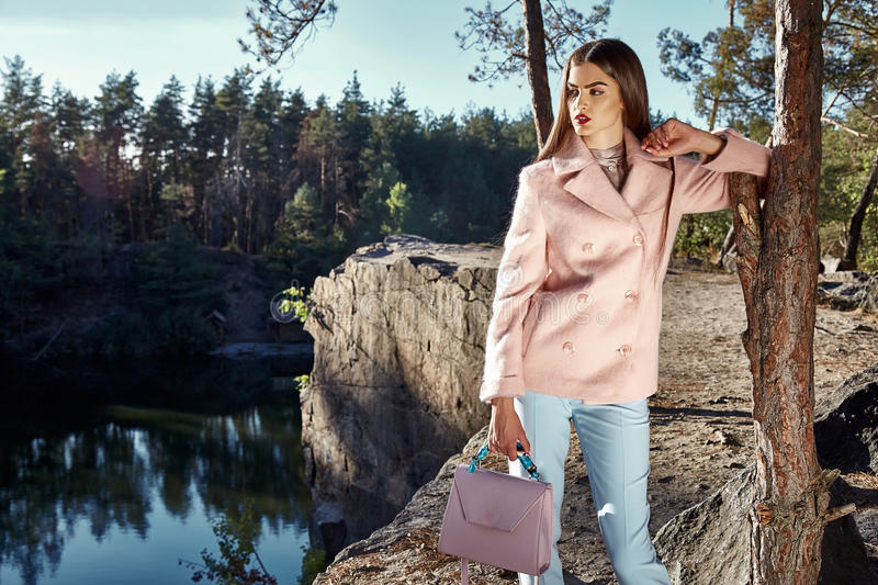 Beautiful woman wear pink color cashmere wool coat. Blue denim jeans autumn brunette hair fashion catalogue accessory bag in forest park walk tree and lake royalty free stock photos