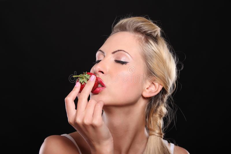 Beautiful young blond woman with strawberry royalty free stock photography