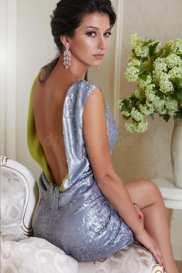 Beautiful young brunette woman with evening make-up chic groomed wearing a short evening dress embroidered with silver. Sequins and earrings sitting on the royalty free stock photography