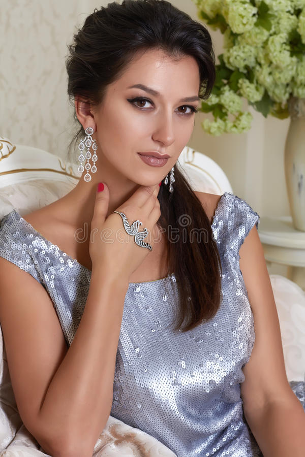 Beautiful young brunette woman with evening make-up chic groomed wearing a short evening dress embroidered with silver. Sequins and earrings sitting on the stock photos