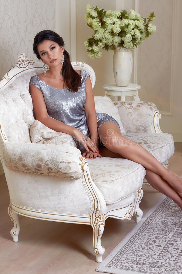 Beautiful young brunette woman with evening make-up chic groomed wearing a short evening dress embroidered with silver. Sequins and earrings sitting on the stock images