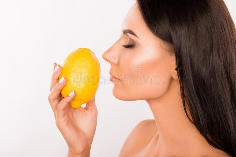 Sexy beautiful young standing in profil woman sniffing the scent of lemon stock photo